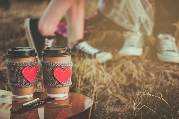 Casal se abraçando enquanto faz piquenique ao pôr do sol xícara de café manga de malha aconchegante com coração de feltro vermelho