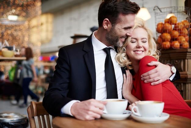 Casal se abraçando na cafeteria