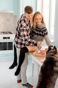 Casal se abraçando na cozinha comendo pizza