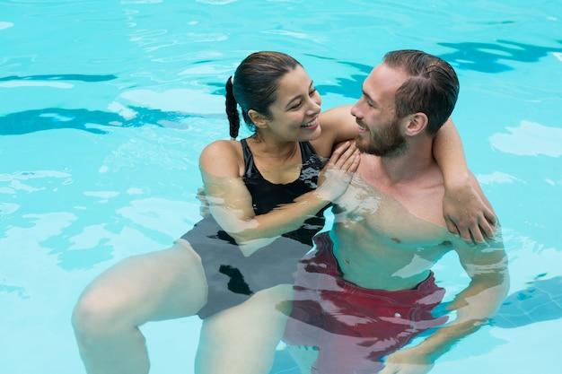 Casal se abraçando na piscina