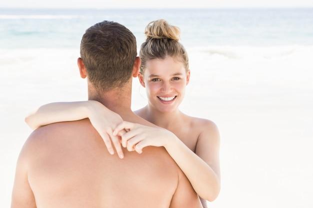 Casal se abraçando na praia