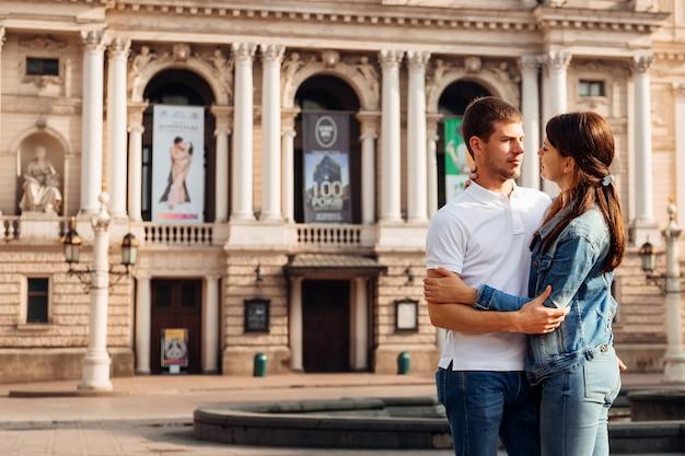 Casal se abraçando no cenário de uma obra-prima arquitetônica