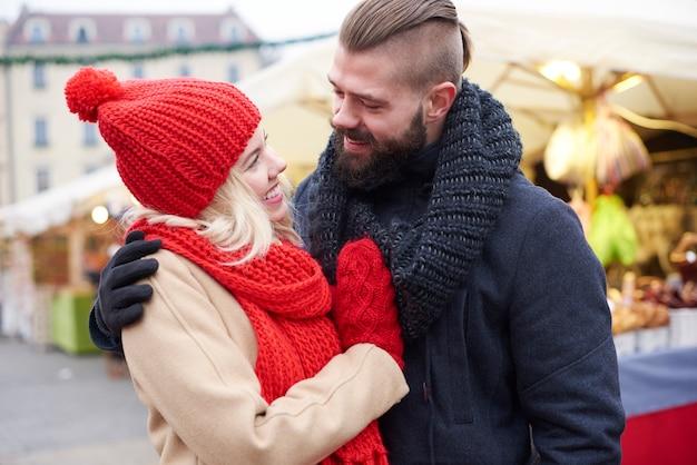 Casal se abraçando no mercado de natal