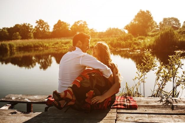 Casal se abraçando olhar para o lago