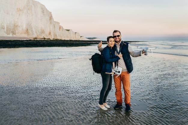 Casal se abraçando, operar com drone por controle remont à beira-mar