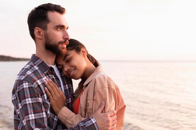 Casal se abraçando perto do mar