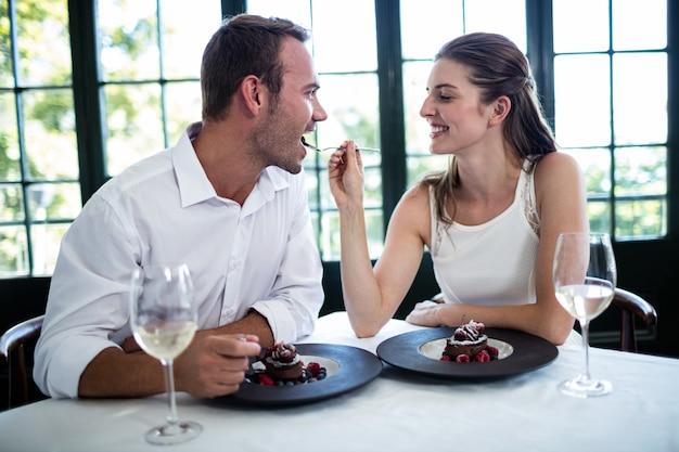 Casal se alimentando e sorrindo