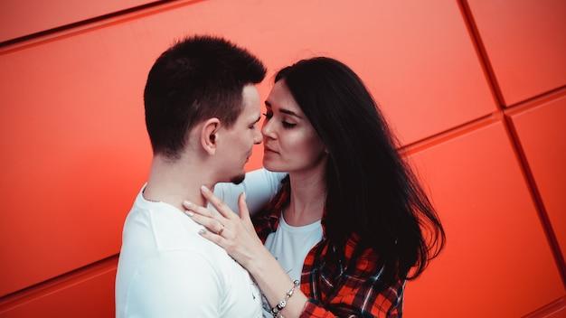 Casal se beijando contra parede vermelha isolada na cidade