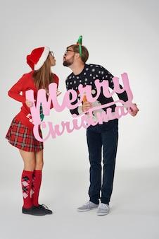 Casal se beijando e segurando uma faixa de natal