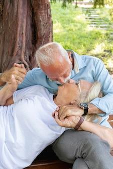 Casal se beijando em um banco no parque