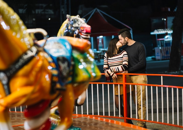 Casal se beijando em um parque temático