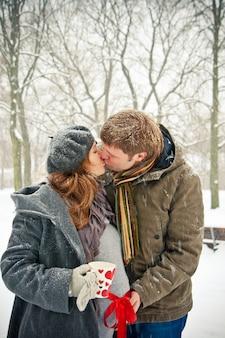 Casal se beijando enquanto a nevar