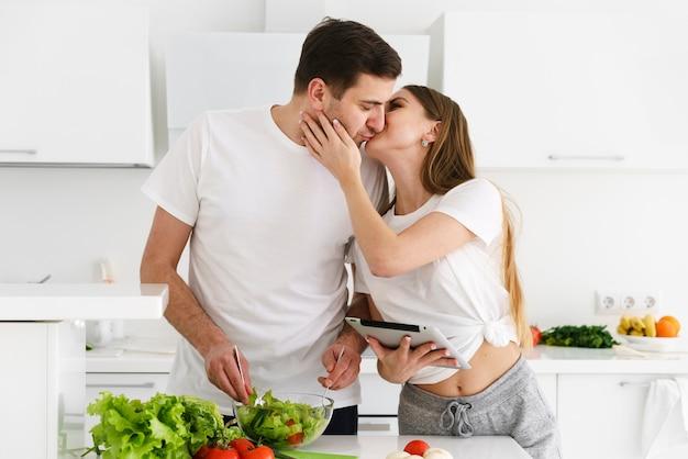 Casal se beijando enquanto cozinhava