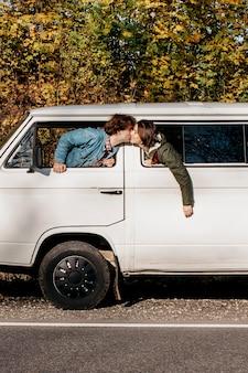 Casal se beijando na janela de uma van