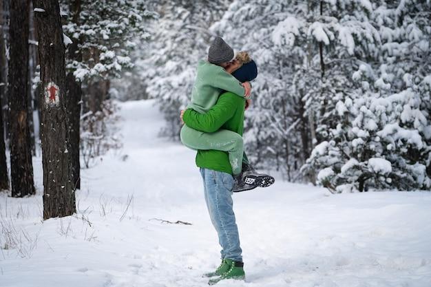 Casal se beijando no parque coberto de neve ao ar livre durante o inverno