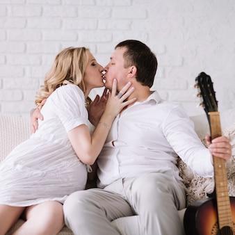 Casal se beijando sentado no sofá em uma aconchegante sala de estar