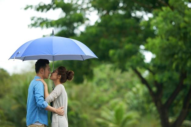 Casal se beijando sob o guarda-chuva