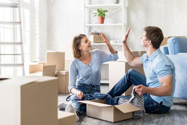 Casal se cumprimentando enquanto fazem as malas para mudar de casa