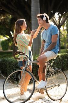 Casal se divertindo ao ar livre com uma bicicleta