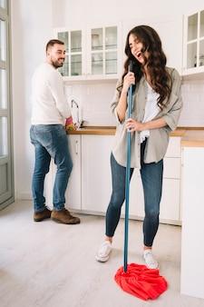 Casal se divertindo ao lavar a cozinha