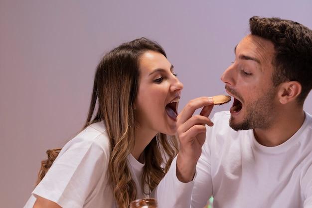 Casal se divertindo com biscoitos