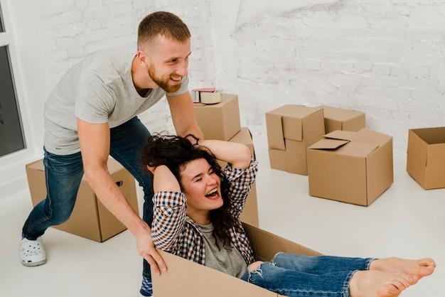 Casal se divertindo com caixa de cartão