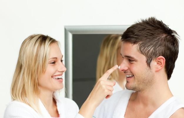 Casal se divertindo com creme no banheiro