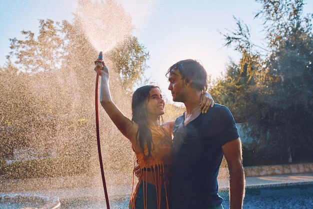 Casal se divertindo despeje um ao outro com mangueira de jardim