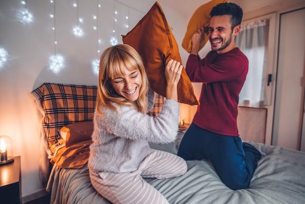 Casal se divertindo enquanto luta de travesseiros na cama