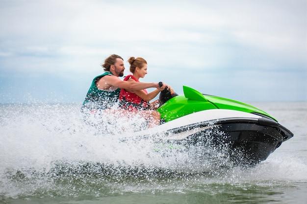 Casal se divertindo na atividade marítima de verão de scooter aquático