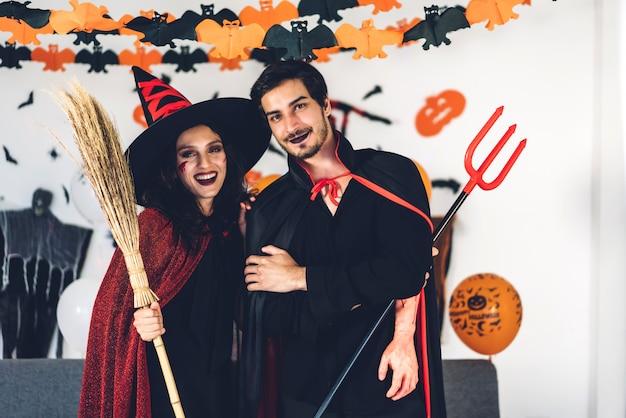 Casal se divertindo segurando abóboras e vestindo fantasias de carnaval vestido de carnaval e maquiagem posando com morcegos e balões