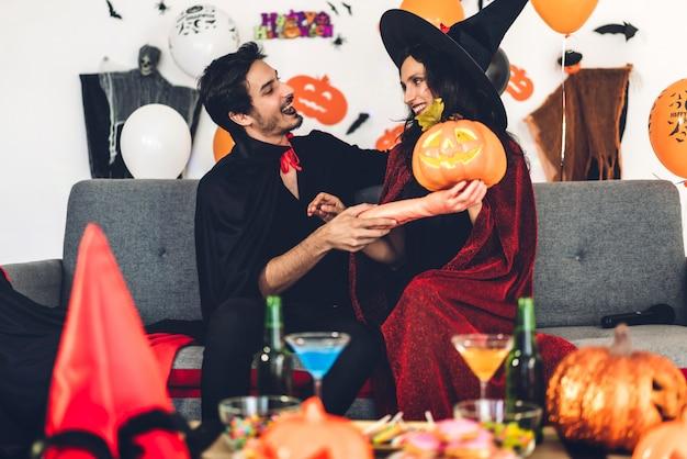 Casal se divertindo segurando abóboras e vestindo trajes de halloween de carnaval vestido e maquiagem posando com morcegos e balões no fundo na festa de halloween. conceito de celebração de feriado do dia das bruxas