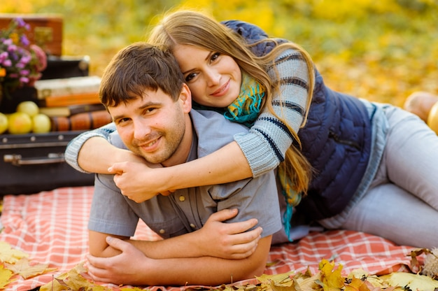 Casal se divertir juntos no parque outono. os amantes jazem em uma manta. uma mulher abraça um homem pelo pescoço de cima.