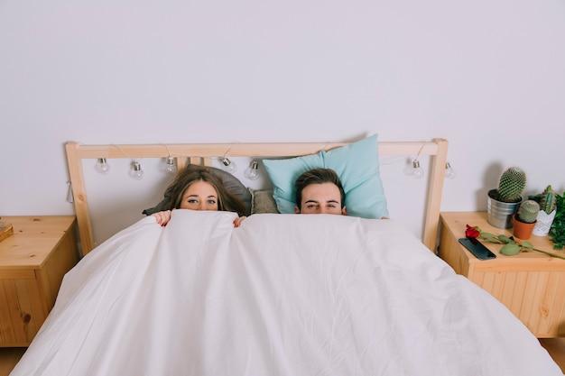Casal se esconde debaixo do cobertor