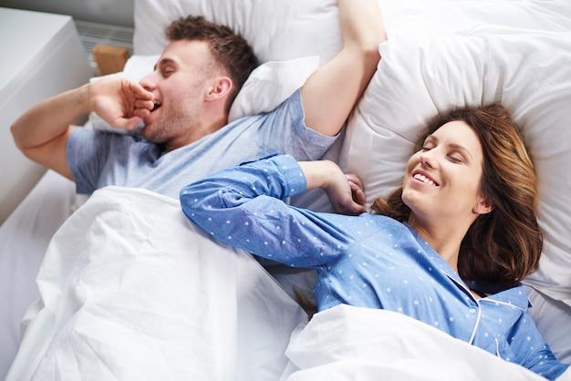 Casal se espreguiçando e bocejando na cama