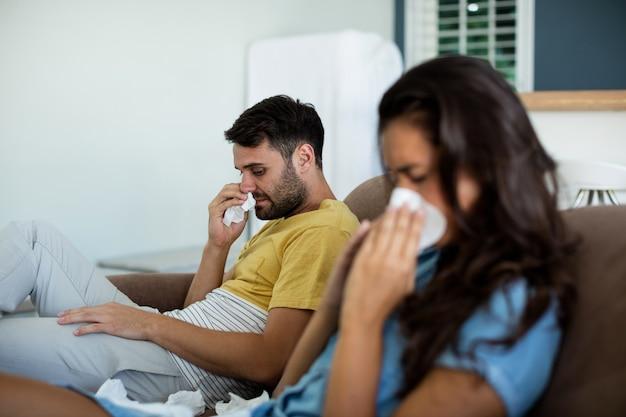 Casal se ignorando na sala de estar de casa