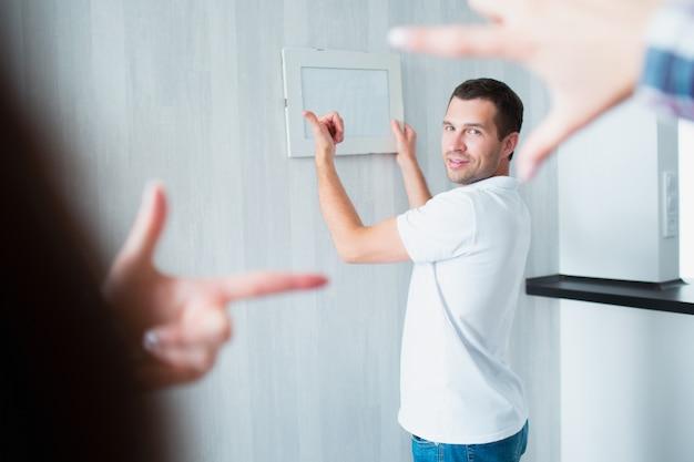Casal se mudou para casa nova. foto de close-up de mãos femininas durante a decoração de apartamento novo, homem pendurado foto ou moldura na parede