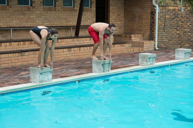 Casal se preparando para mergulhar na piscina