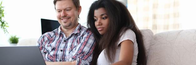 Casal se senta no sofá em casa e olha para o laptop. homem de pele branca sorri, segura o laptop no colo e aponta o dedo para a tela. mulher negra sentada em posição reclinada ao lado do marido.