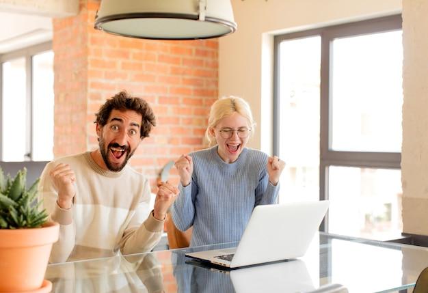 Casal se sentindo chocado, animado e feliz, rindo e comemorando o sucesso, dizendo uau!