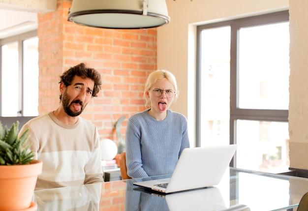 Casal se sentindo enojado e irritado, mostrando a língua, não gostando de algo desagradável e nojento