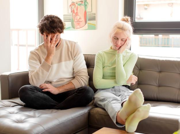 Casal se sentindo entediado, frustrado e com sono depois de uma tarefa cansativa, enfadonha e tediosa, segurando o rosto com a mão
