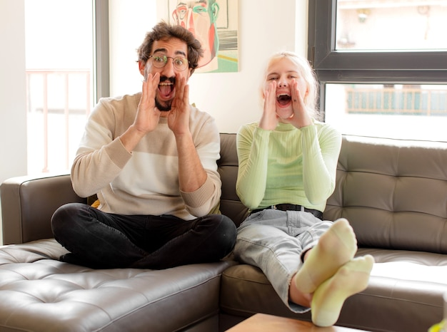 Casal se sentindo feliz, animado e positivo, dando um grande grito com as mãos perto da boca, gritando