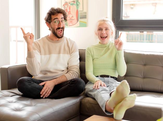 Casal se sentindo um gênio feliz e animado depois de realizar uma ideia, levantando o dedo alegremente, eureka!