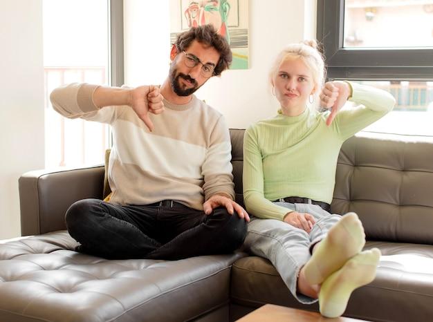 Casal se sentindo zangado, irritado, irritado, desapontado ou insatisfeito, mostrando o polegar para baixo com um olhar sério