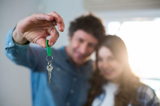 Casal segurando a chave da nova casa