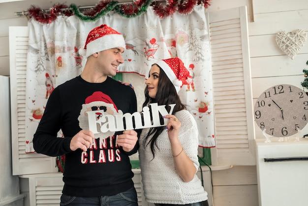 Casal segurando a palavra 'família' e olhando um para o outro