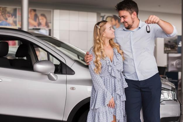 Casal segurando as chaves do carro e olhando um ao outro