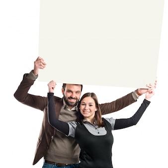 Casal segurando cartaz sobre fundo branco