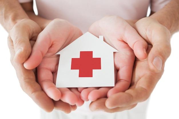 Casal segurando casa de papel com cruz vermelha nas mãos